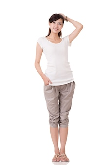 Enthousiaste jeune femme asiatique posant, portrait en pied sur fond blanc.
