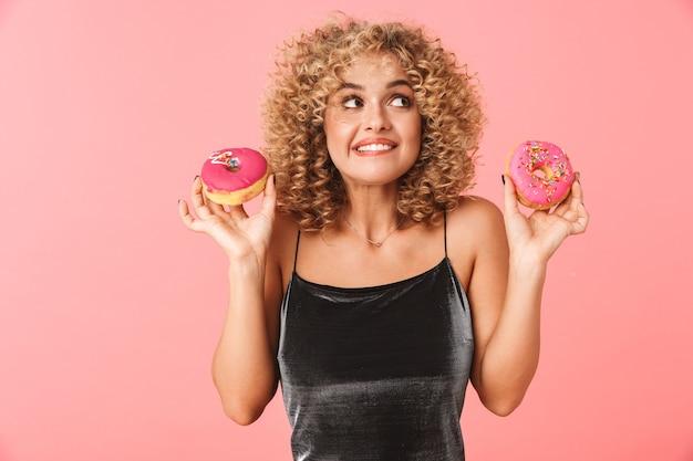 Enthousiaste jeune femme aux cheveux bouclés, manger des beignets glacés