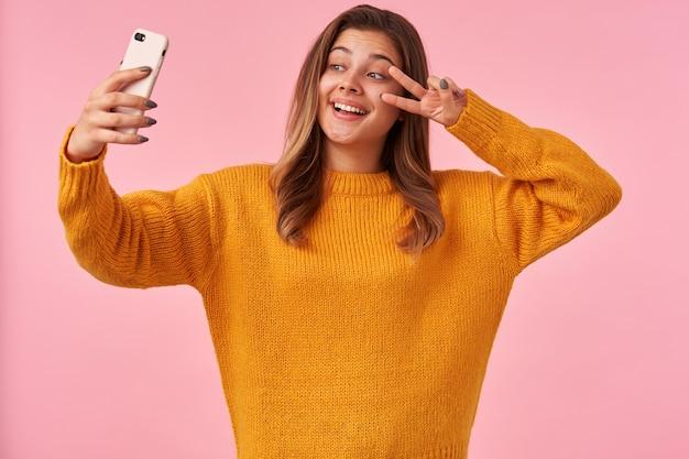 Enthousiaste jeune femme aux cheveux bruns, levant la main avec le signe de la victoire sur son visage tout en faisant le portrait d'elle-même sur son smartphone, debout sur le rose dans des vêtements décontractés