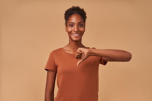 Enthousiaste jeune femme bouclée à la peau sombre avec une coiffure chignon montrant avec le pouce et souriant largement, isolé sur beige
