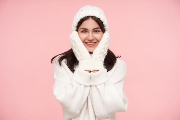 Enthousiaste jeune femme brune aux yeux bruns vêtue de vêtements confortables en laine blanche tenant son visage avec les mains levées et souriant joyeusement à l'avant, isolé sur un mur rose