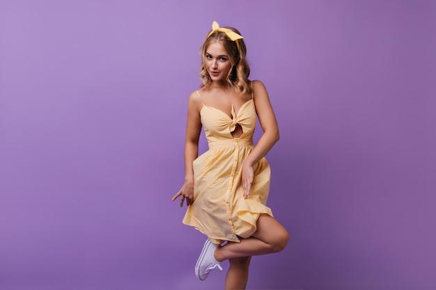 Enthousiaste jeune femme dansant de manière ludique sur violet. jolie fille bouclée exprimant de bonnes émotions pendant la séance de portraits.