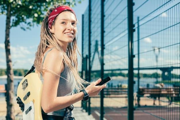 Enthousiaste jeune femme détendue avec des dreadlocks souriant et l'air heureux tout en étant près du terrain de sport avec sa guitare