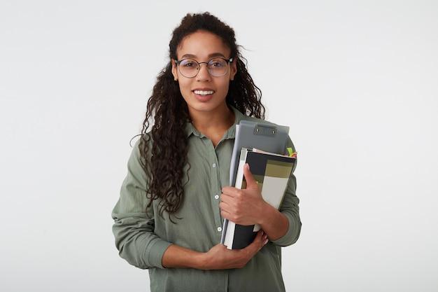 Enthousiaste jeune femme frisée aux cheveux bruns avec une peau foncée tenant des livres tout en regardant volontiers la caméra avec un large sourire, isolé sur fond blanc