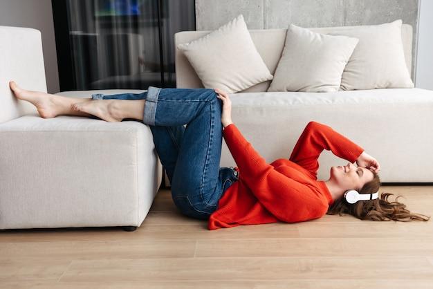Enthousiaste jeune femme habillée avec désinvolture portant sur un sol à la maison, écouter de la musique avec des écouteurs
