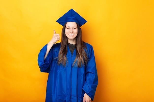 Enthousiaste jeune femme heureuse l'obtention du diplôme portant baccalauréat bleu et montrant le geste du pouce vers le haut
