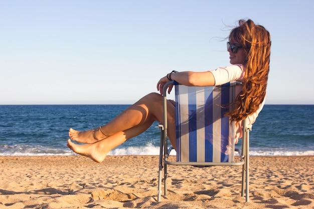 Enthousiaste jeune femme avec des lunettes de soleil avec de longs cheveux roux souriant et relaxant sur la plage de la chaise avec la mer sur fond