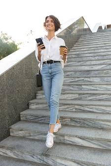 Enthousiaste jeune femme marchant en bas dans la rue