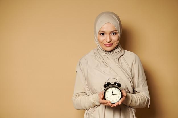 Enthousiaste jeune femme musulmane en hijab tenant un réveil dans les mains et souriant mignon à l'avant debout contre une surface beige avec espace copie