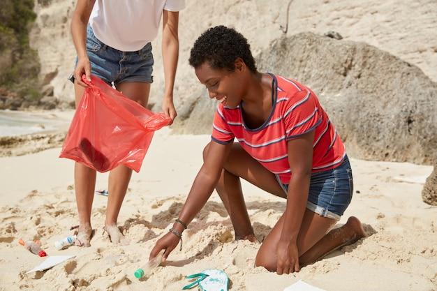 Enthousiaste jeune femme à la peau sombre ramasse des bouteilles en plastique