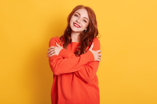 Enthousiaste jeune femme romantique exprime son amour et ses soins, sourit doucement, porte un pull surdimensionné orange, embrasse son propre corps