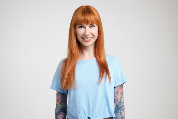 Enthousiaste jeune femme rousse aux cheveux longs avec des tatouages montrant ses dents blanches parfaites tout en souriant joyeusement à la caméra, isolé sur fond blanc