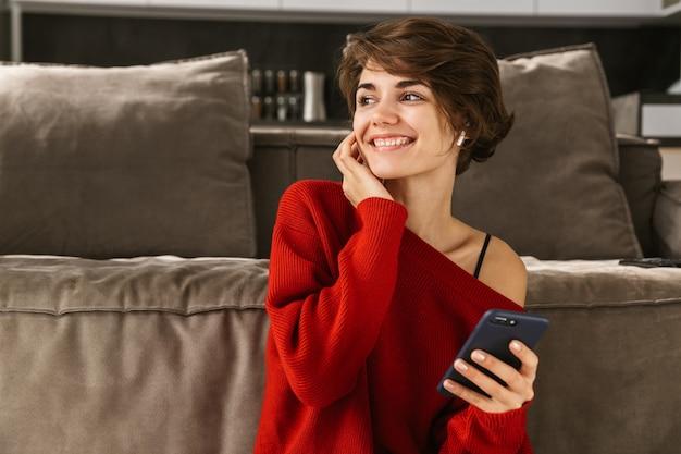 Enthousiaste jeune femme se détendre à la maison, écouter de la musique avec des écouteurs sans fil