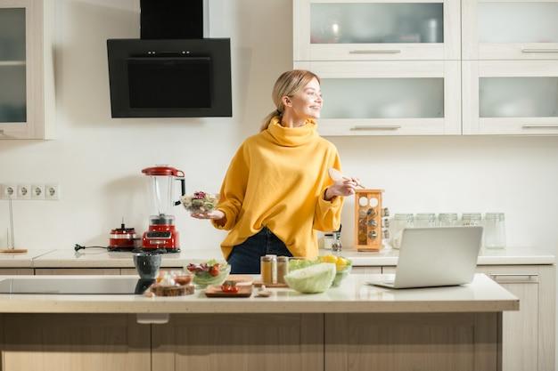 Enthousiaste jeune femme se sentant ravie et souriante en se tenant debout dans la cuisine avec salade et bol en bois tout en regardant au loin