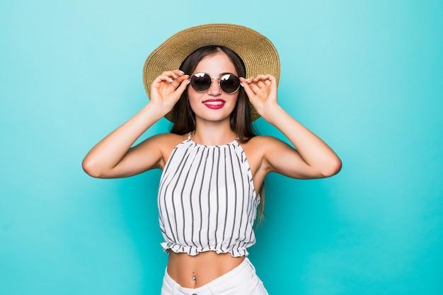 Enthousiaste jeune femme séduisante à lunettes de soleil et chapeau sur fond turquoise