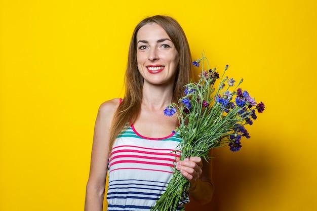 Enthousiaste jeune femme souriante dans une robe rayée avec un bouquet de fleurs