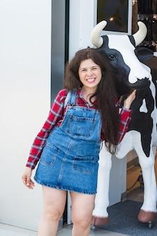 Enthousiaste jeune femme avec une statue de tête de vache en face de la boutique.