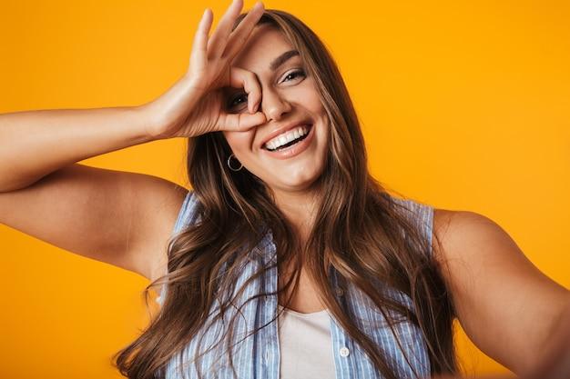 Enthousiaste jeune femme en surpoids, prenant un selfie