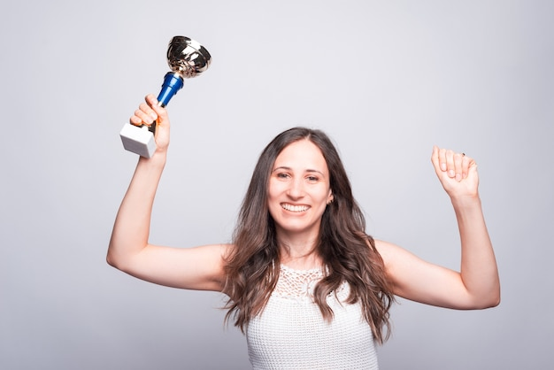 Enthousiaste jeune femme tenant le prix de la coupe, célébrant le succès