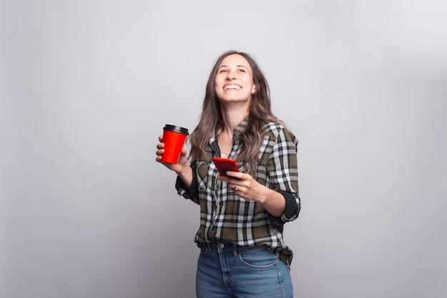 Enthousiaste jeune femme tient une tasse avec une boisson chaude et un téléphone près du mur gris