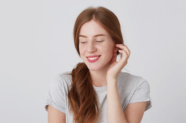 Enthousiaste jeune femme timide aux cheveux rouges et taches de rousseur porte un t-shirt gris souriant et regardant vers le bas