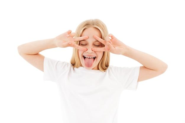 Enthousiaste jeune fille blonde dans des vêtements décontractés s'amusant tout en tenant les bras sur le visage comme un masque et en montrant sa langue sur blanc