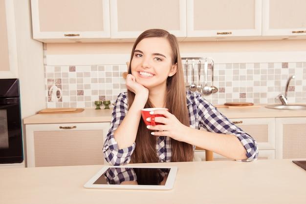Enthousiaste jeune fille buvant du café dans la cuisine avec tablette