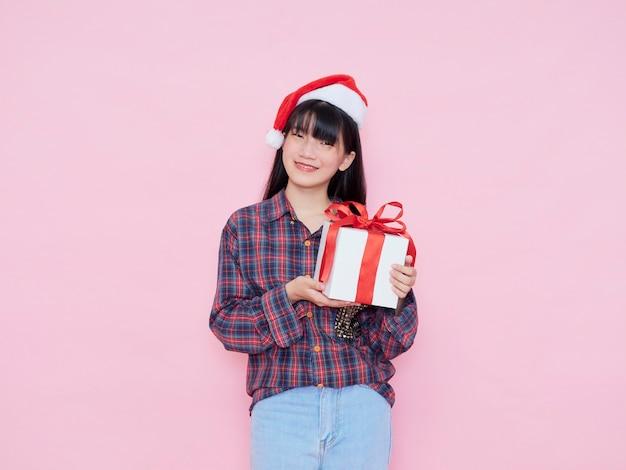 Enthousiaste jeune fille portant bonnet de noel avec boîte-cadeau sur fond rose
