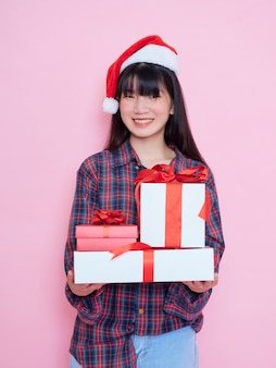 Enthousiaste jeune fille portant bonnet de noel avec des coffrets cadeaux sur fond rose