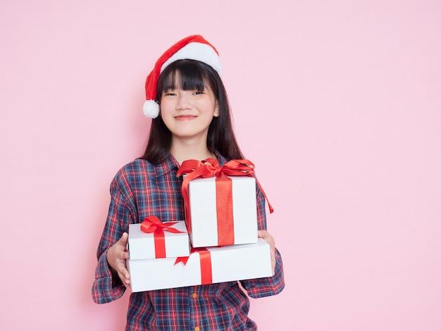 Enthousiaste jeune fille portant bonnet de noel avec des coffrets cadeaux sur rose