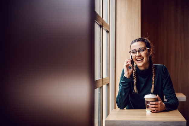 Enthousiaste jeune fille souriante assise à la cafétéria, ayant une conversation téléphonique et tenant une tasse jetable avec du café frais.