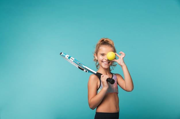 Enthousiaste jeune fille sportive jouant au tennis isolé sur mur bleu