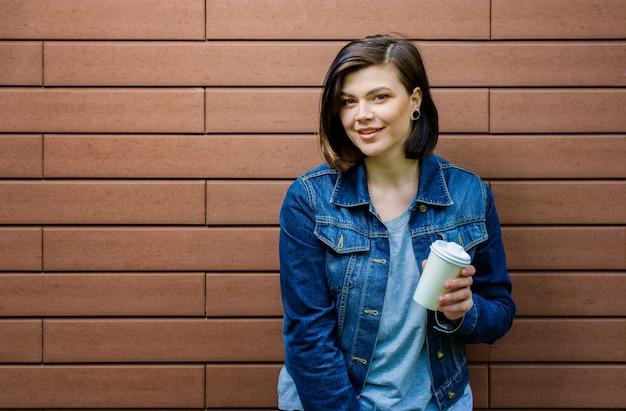 Enthousiaste jeune fille avec une tasse de café à la main sur un mur de briques. une femme dans une veste en jean bleu et avec des yeux dans ses oreilles.