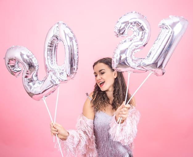Enthousiaste jeune fille en tenue de fête sur fond de studio rose posant tenant des ballons d'argent pour le concept de nouvel an