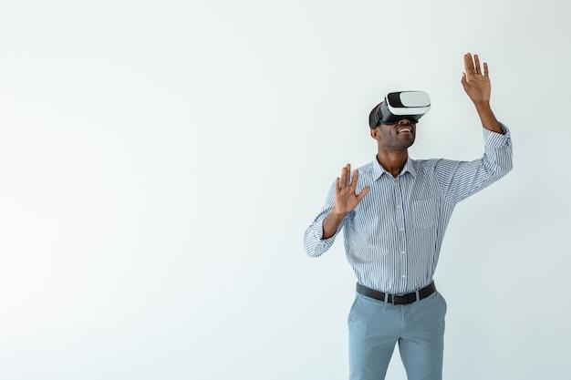 Enthousiaste jeune homme d'affaires afro-américain portant des lunettes de réalité virtuelle tout en le testant