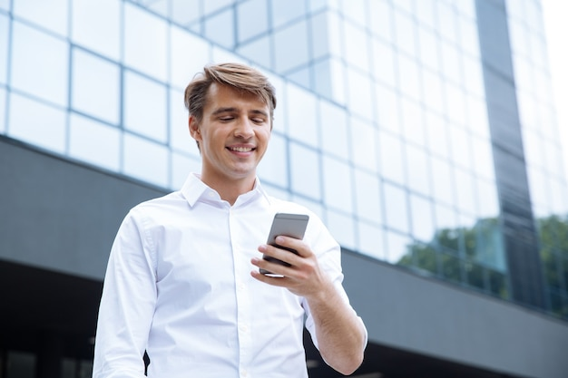 Enthousiaste jeune homme d'affaires à l'aide de smartphone près du centre d'affaires