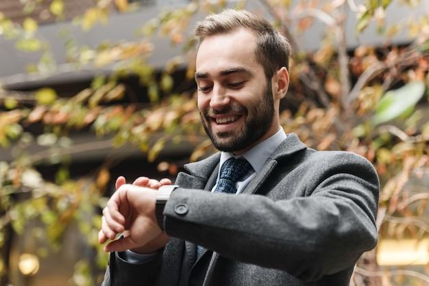 Enthousiaste jeune homme d'affaires portant costume marchant à l'extérieur, vérifier l'heure