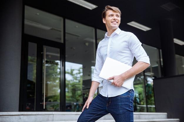 Enthousiaste jeune homme d'affaires près du centre d'affaires