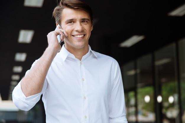 Enthousiaste jeune homme d'affaires souriant et parlant au téléphone portable dans la rue