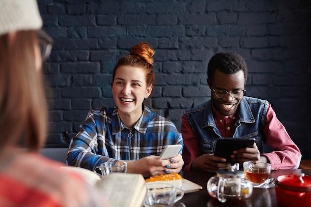 Enthousiaste jeune homme africain portant des lunettes élégantes et jolie femme de race blanche aux cheveux roux ayant une conversation de souris avec une fille brune méconnaissable devant eux