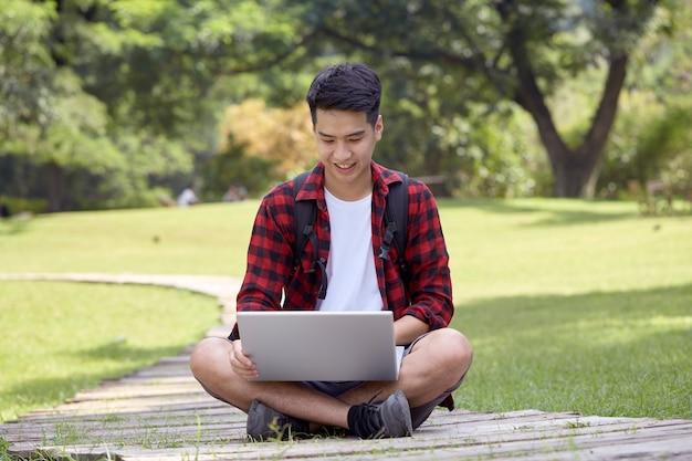 Enthousiaste jeune homme assis dans le parc et à l'aide d'un ordinateur portable