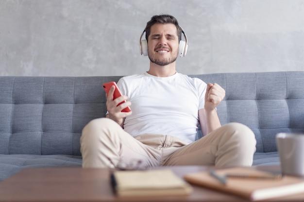 Enthousiaste jeune homme au casque d'écoute de la musique tout en étant assis sur son canapé à la maison