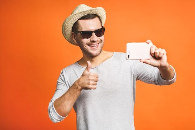Enthousiaste jeune homme au chapeau et lunettes de soleil prenant selfie avec smartphone