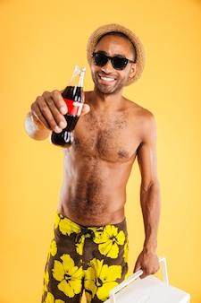 Enthousiaste jeune homme au chapeau et lunettes de soleil tenant une bouteille de coke et un sac isotherme sur un mur orange