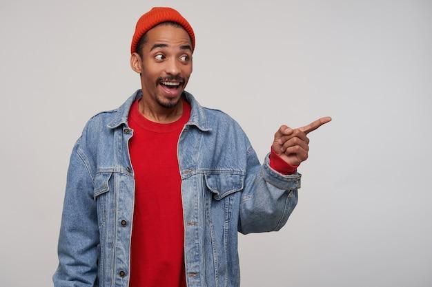 Enthousiaste jeune homme aux cheveux brun barbu attrayant avec une peau sombre montrant de côté avec l'index levé et souriant joyeusement en se tenant debout sur un mur blanc