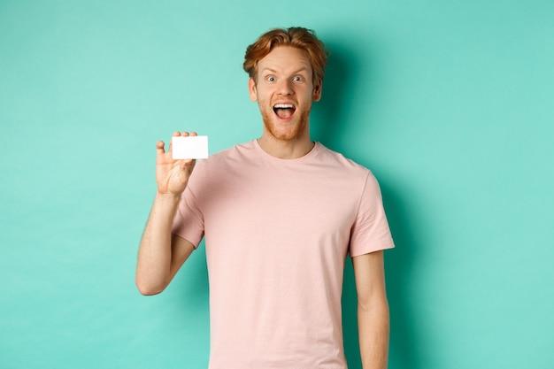 Enthousiaste jeune homme aux cheveux roux et à la barbe, portant un t-shirt, montrant une carte de crédit en plastique et souriant à la caméra, montre une nouvelle promotion bancaire.