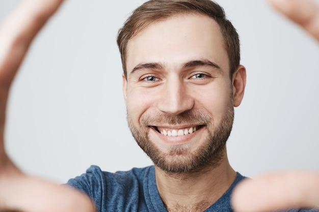 Enthousiaste jeune homme avec barbe, souriant prenant selfie