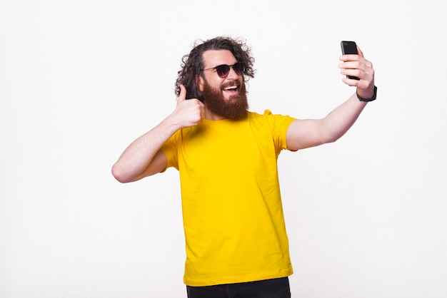 Enthousiaste jeune homme barbu fait un selfie dans un studio.