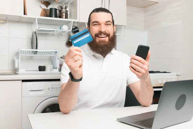 Enthousiaste jeune homme barbu hipster assis dans la cuisine et payer en ligne avec carte de crédit et smartphone