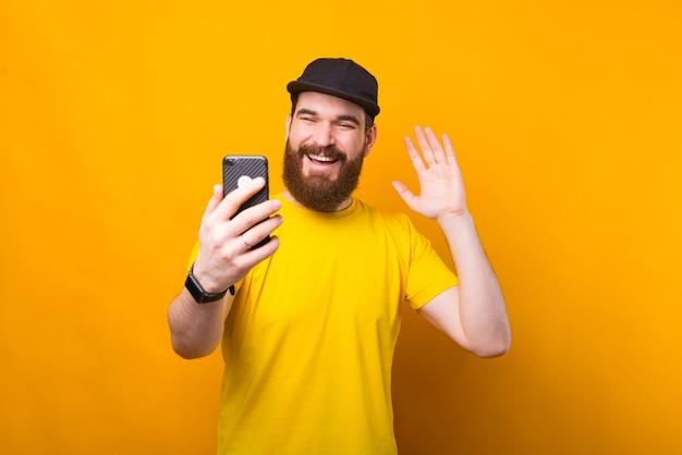 Enthousiaste jeune homme barbu parle avec quelqu'un sur appel vidéo